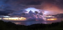 Dramatic sunset with storm in background, and lightening (on right side). Caribbean sea view in Dominica, Lesser Antiles. Sept. 2019. Stitched panorama.